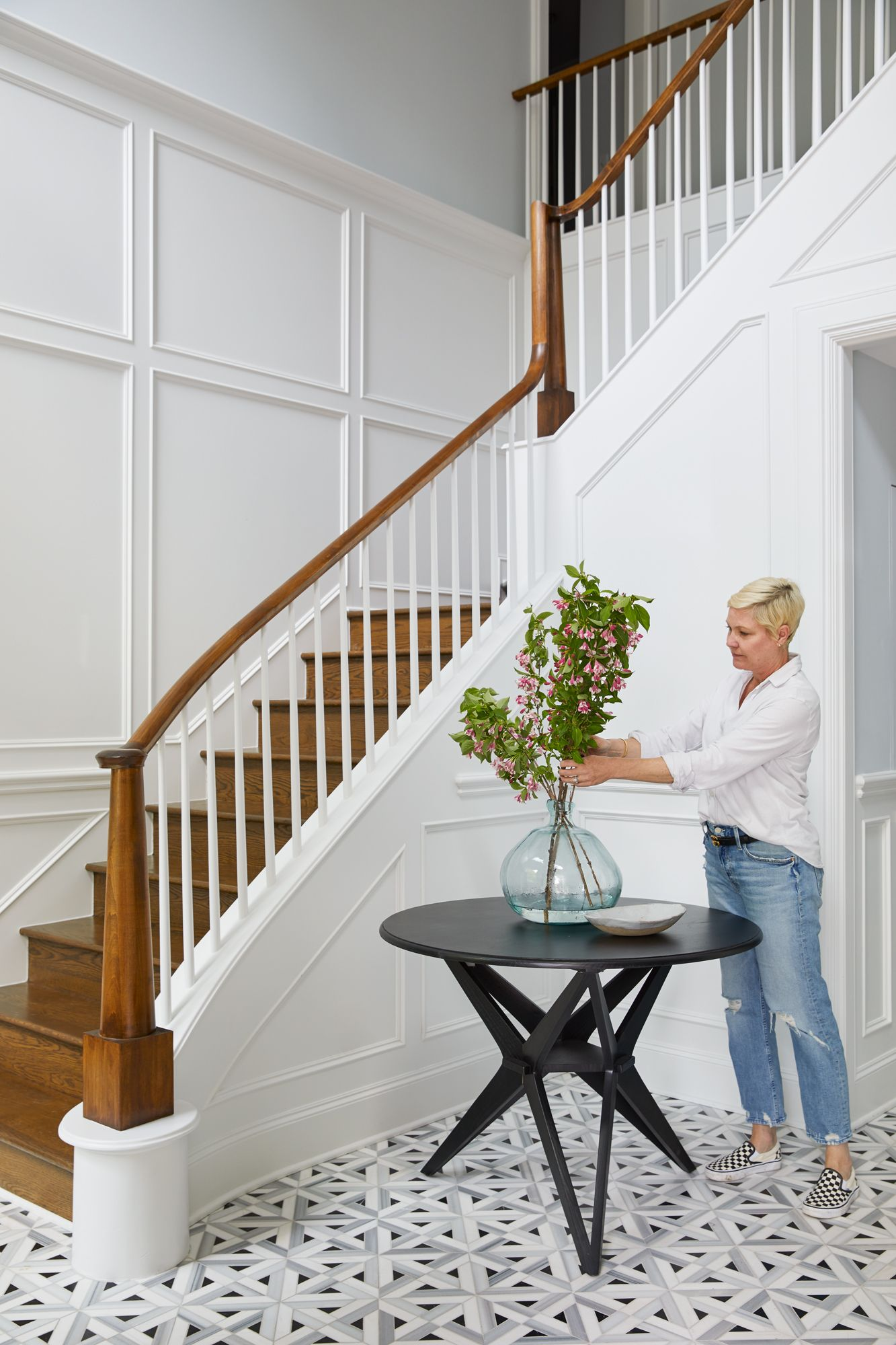 Portrait of a woman arranging flowers in entryway