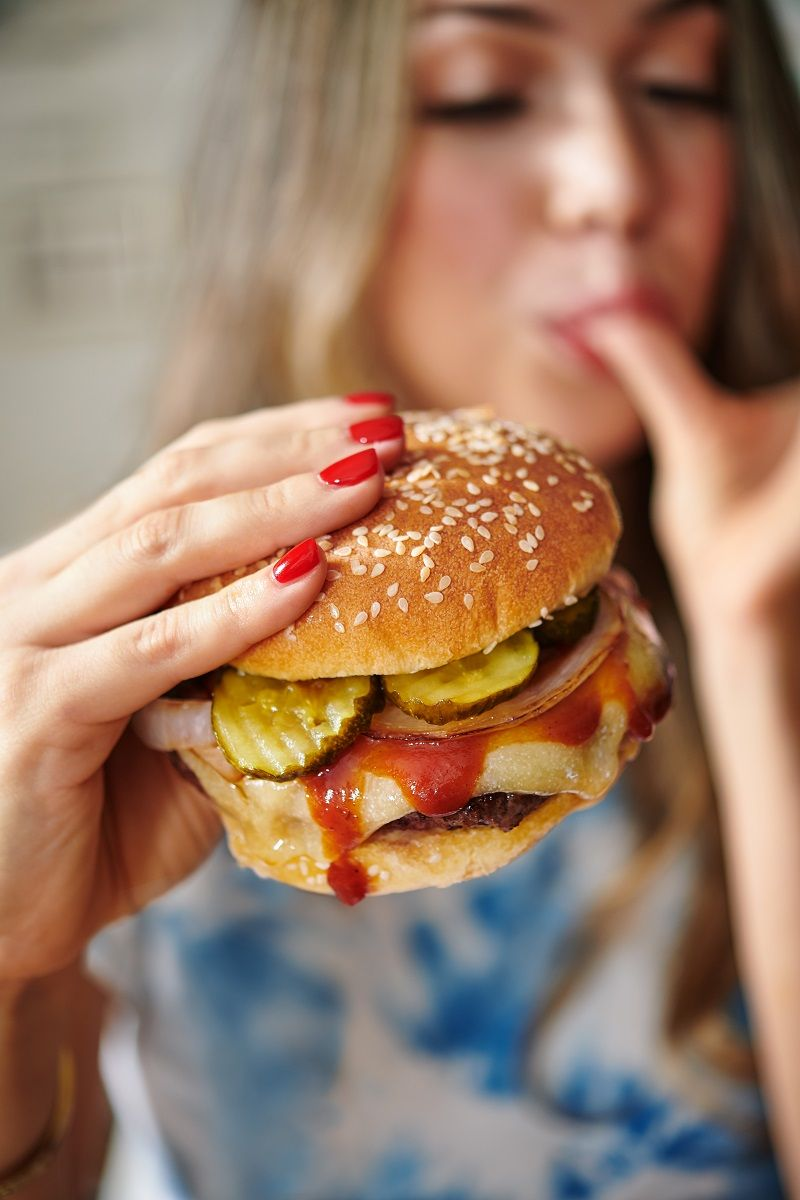 Teen age girl eating a cheeseburger