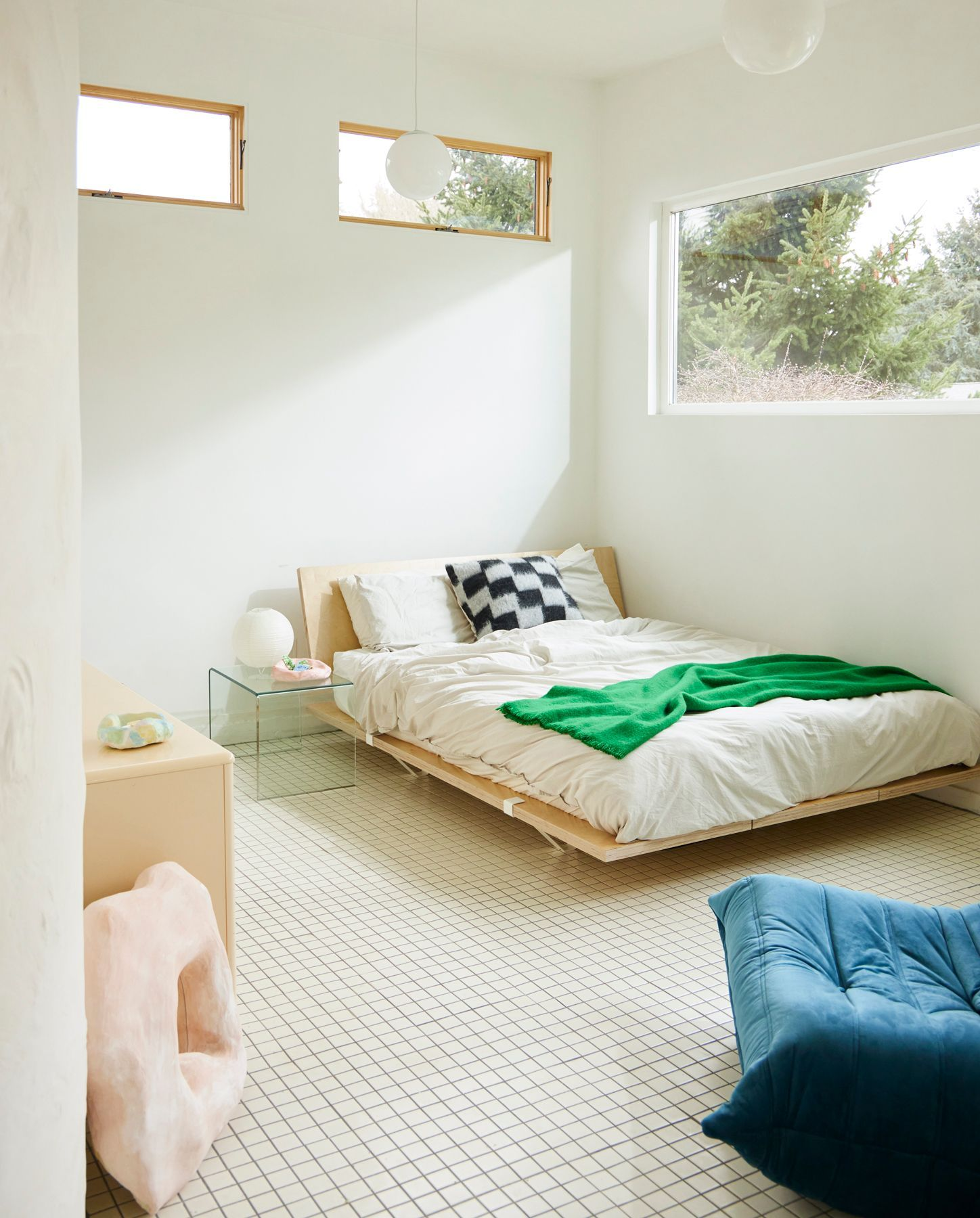 white bedroom with green blanket