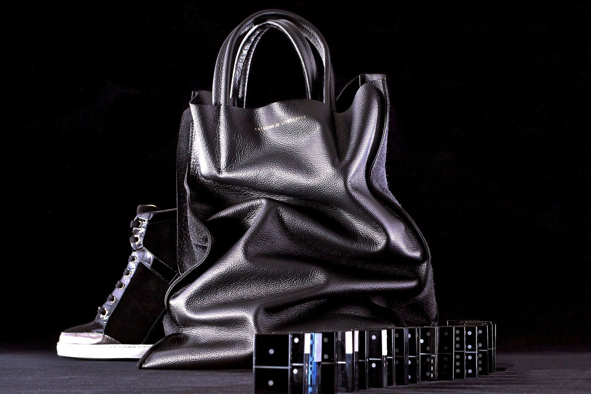 Shiny black leather bag and dominos