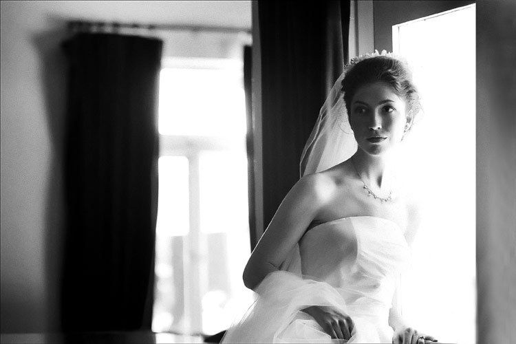 A bride  looks out the window on her wedding in Los Angeles wedding  photo