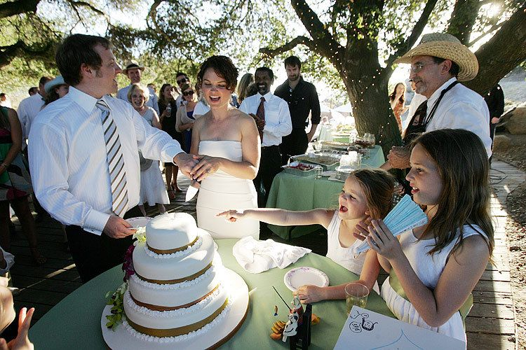 Malibu wedding photo by Issa Sharp. A Los Angeles wedding couple cutting their cake at the wedding reception
