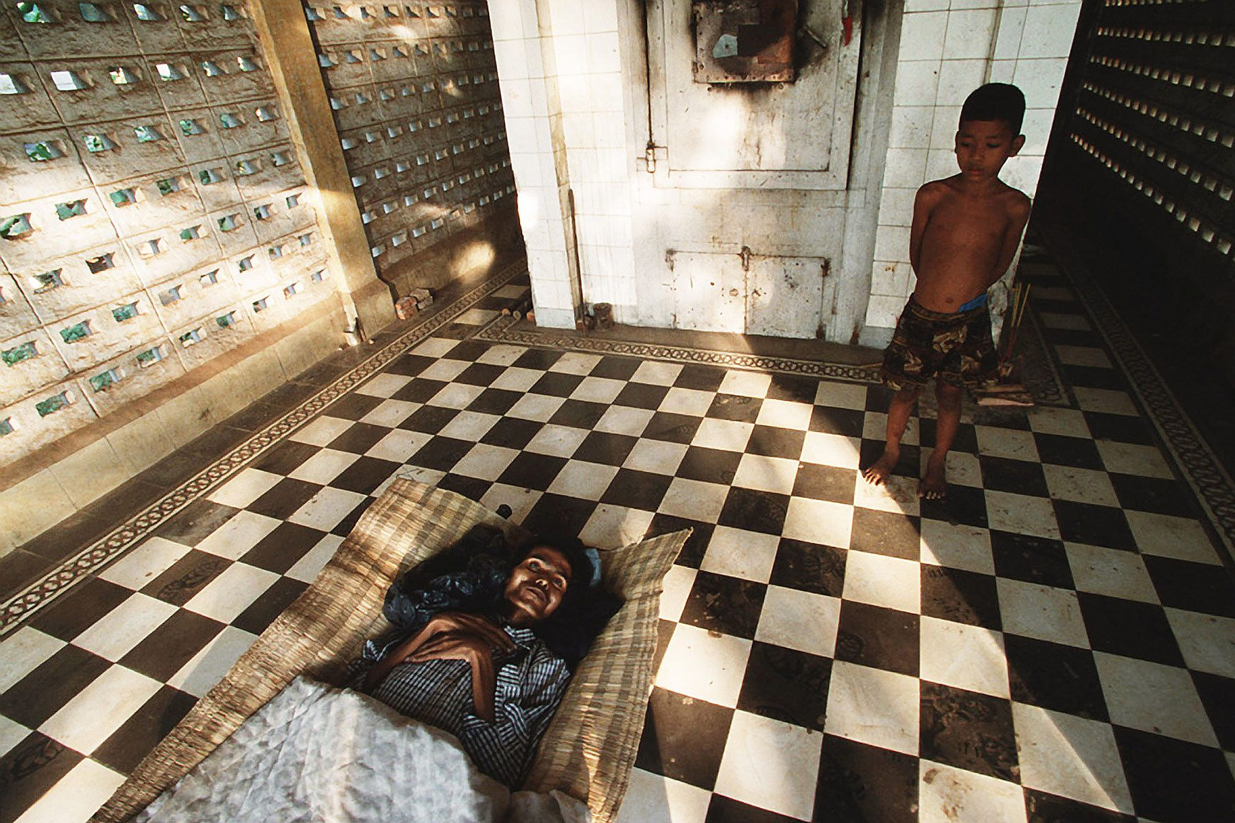 A boy waits for cremation of his father, who died in Aids ward. He became an orphan.