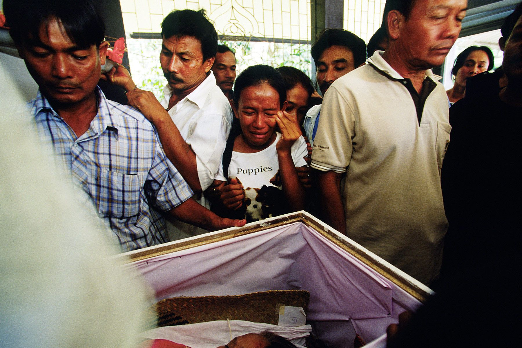 A daughter cries during a funeral of her mother at Buddhist temple.