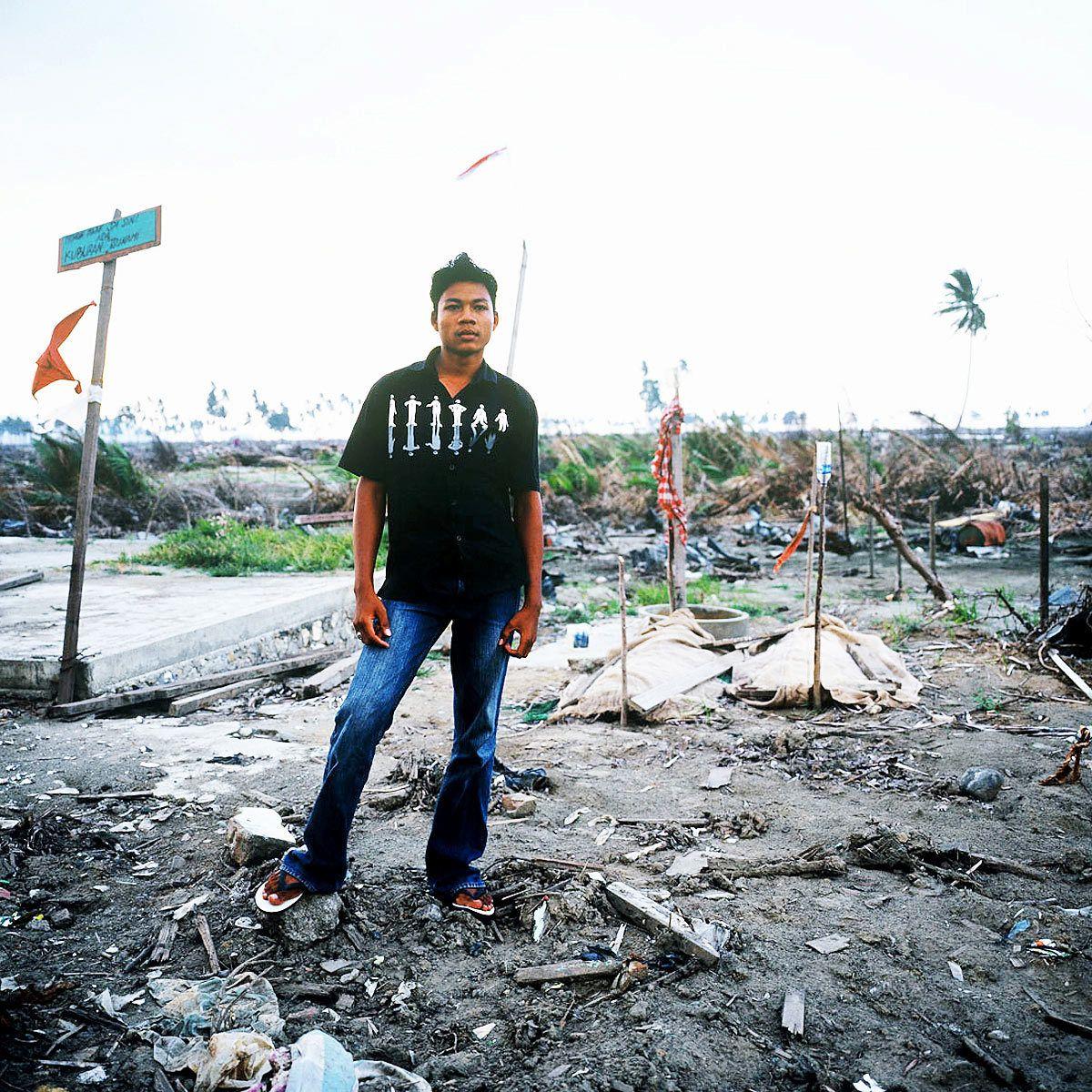 Amri stands in front of his family's gravesBanda Ache © 2004 Masaru Goto
