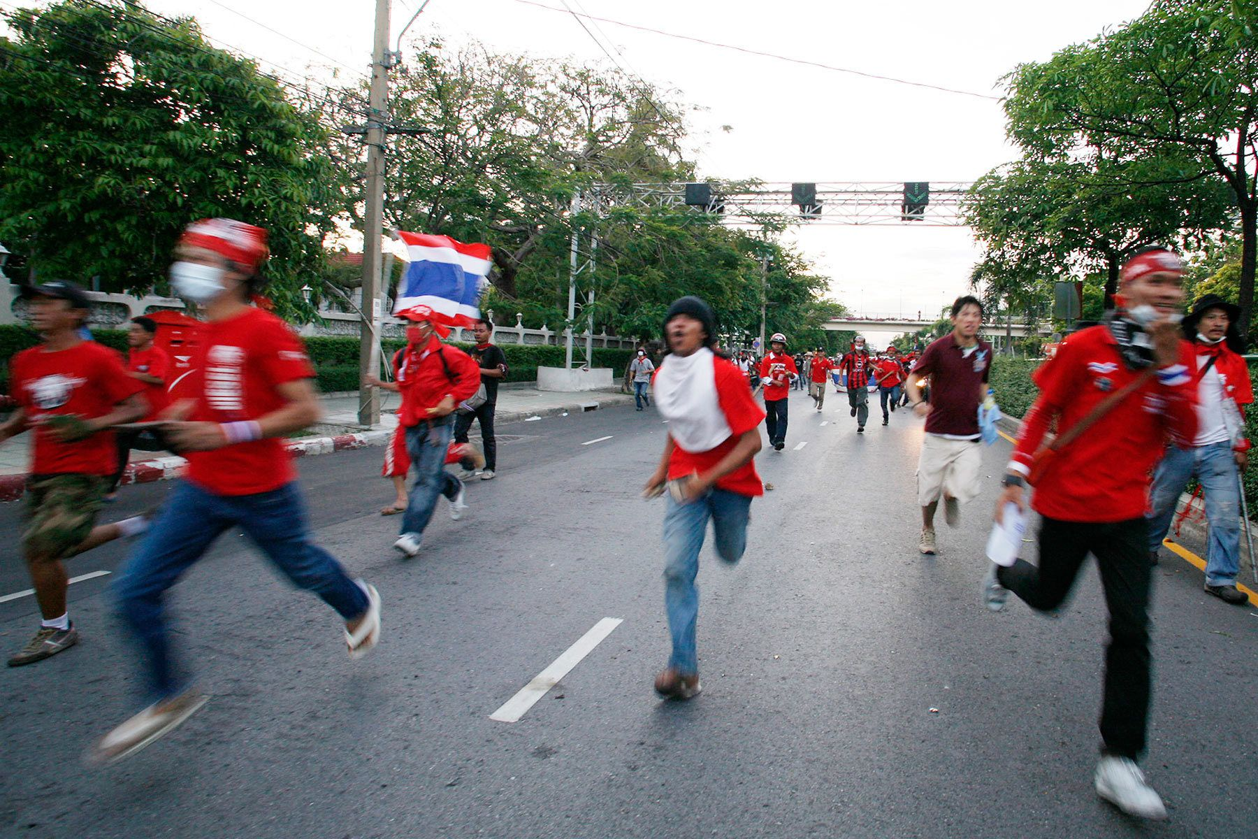Members of the anti-government United Front for Democracy against Dictatorship (UDD) run during a street fight against residents in Bangkok.