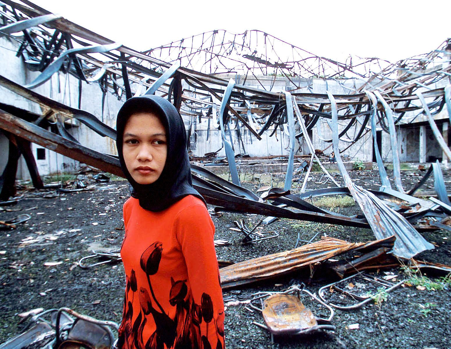 """A student stands in front of her University Hall, which was recently burned down.When I asked people, """"Who did this?""""They always answer,""""A person who has no name """"Syiah Kuala University."""