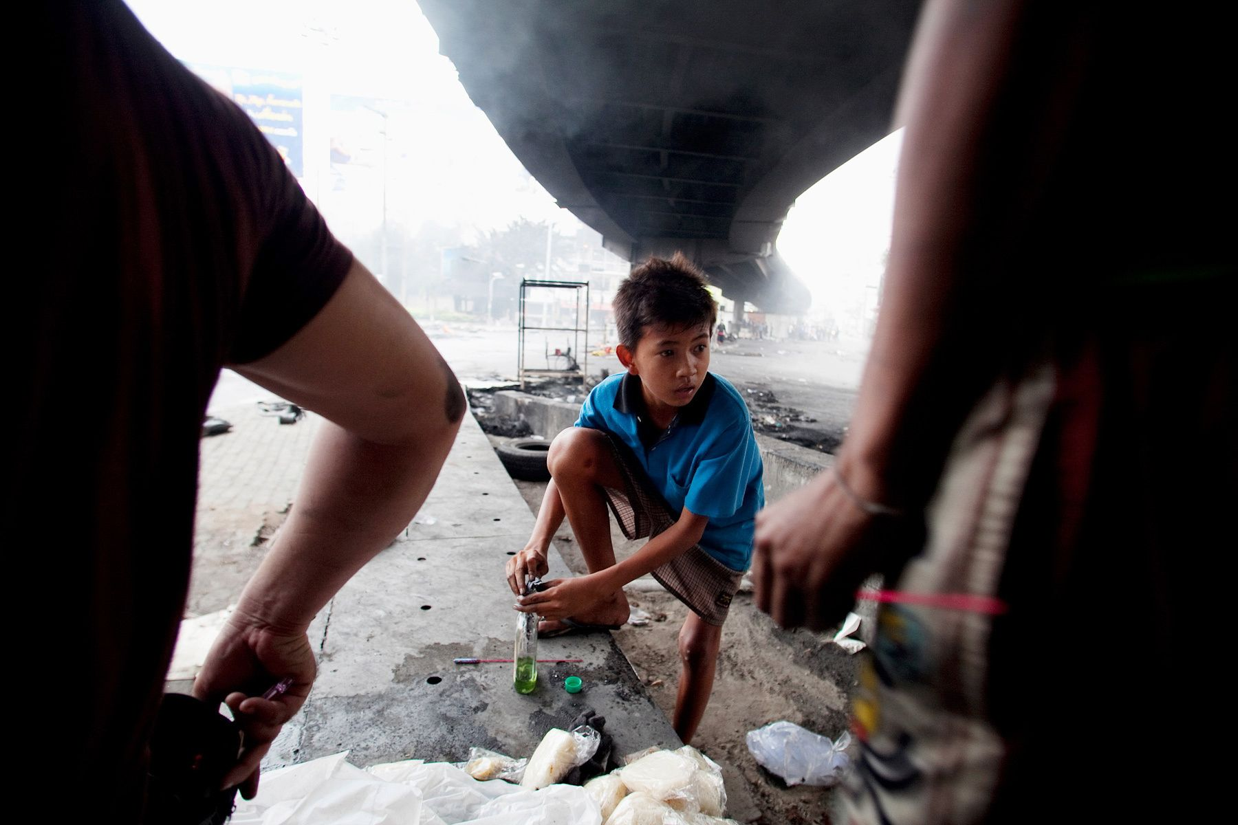A young boy helps members of The United Front for DemocracyAgainst Dictatorship (UDD) prepare Molotov cocktails to throw atsoldiers.