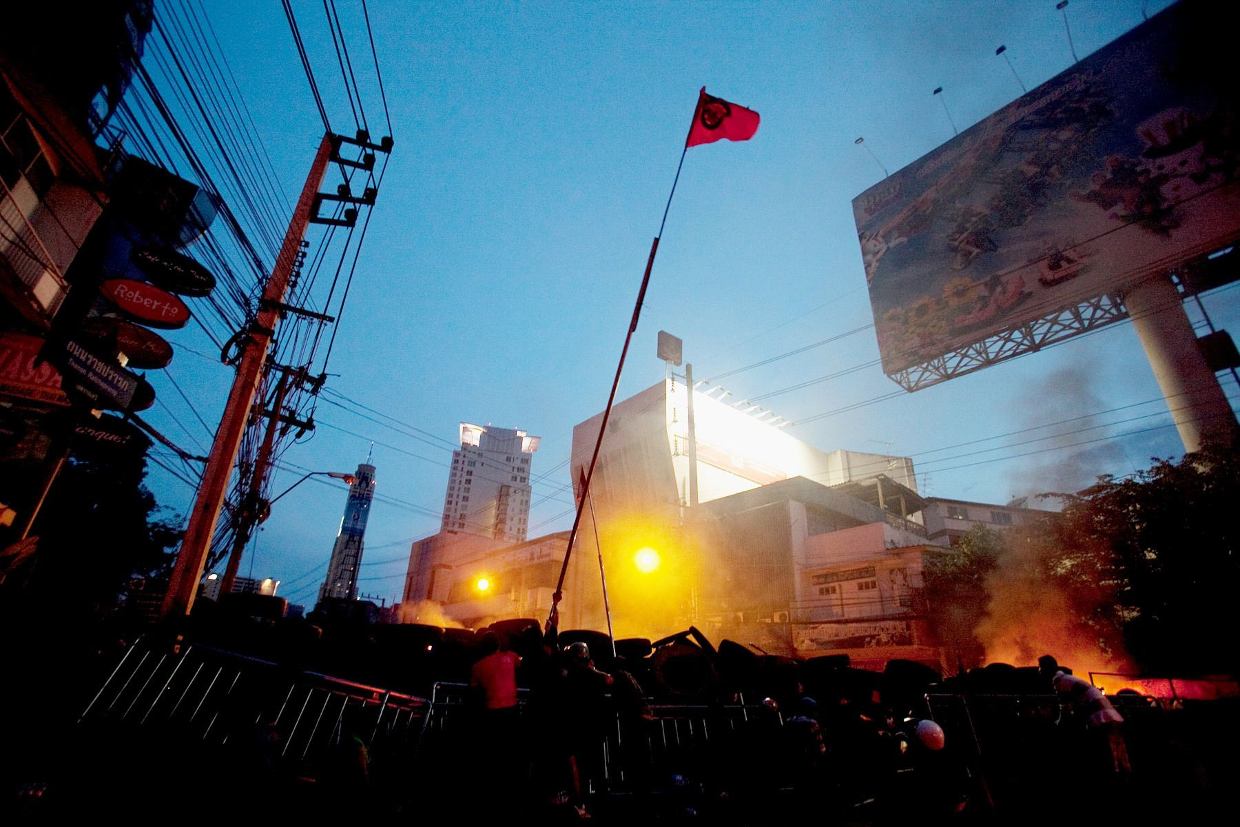 Members of the United Front for Democracy Against Dictatorship(UDD) fly a red flag during a clash with soldiers.
