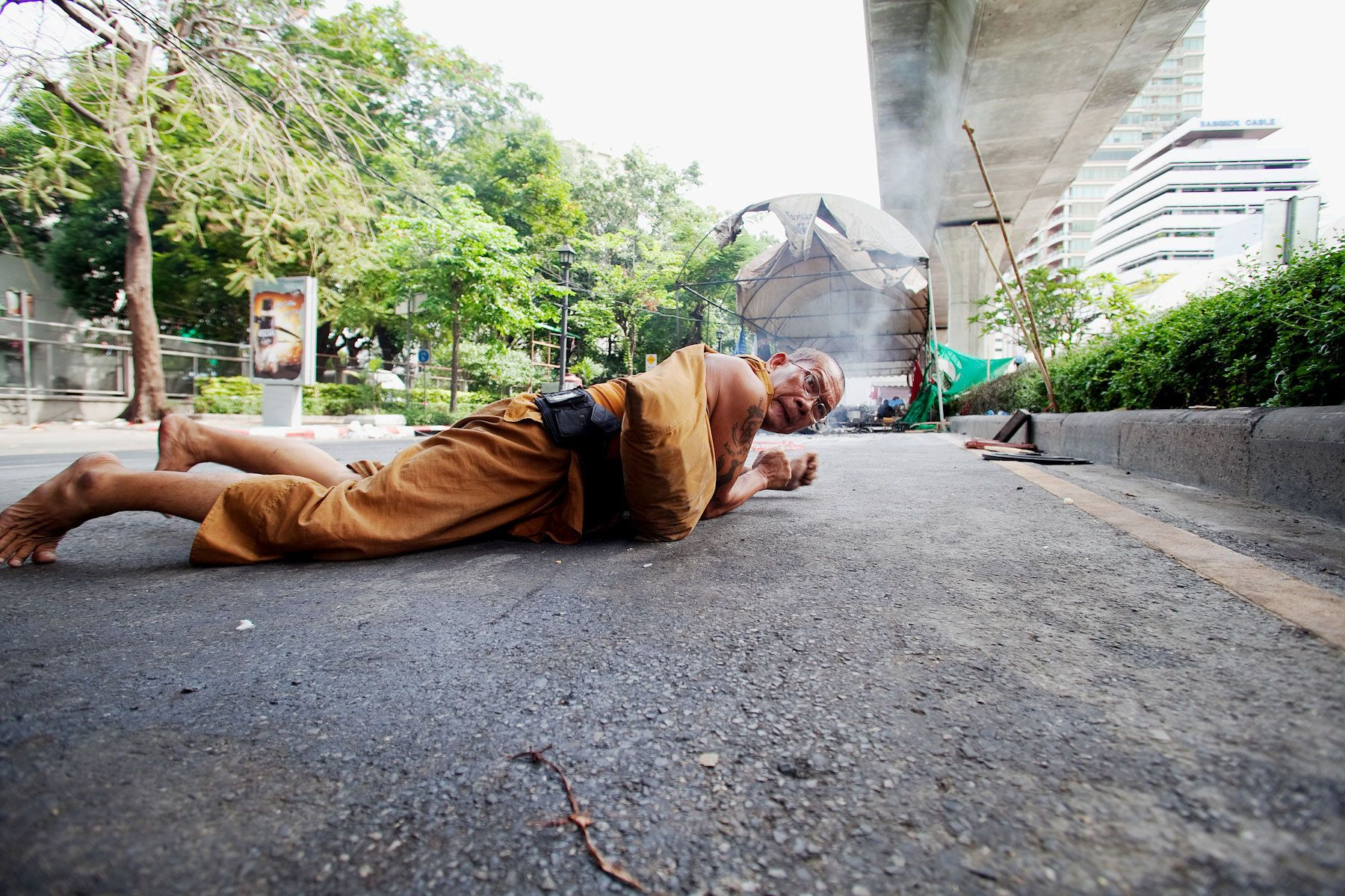 A monk supporter of The United Front for Democracy AgainstDictatorship (UDD) takes cover from heavy gunfire during the military crackdown against UDD demonstrators.