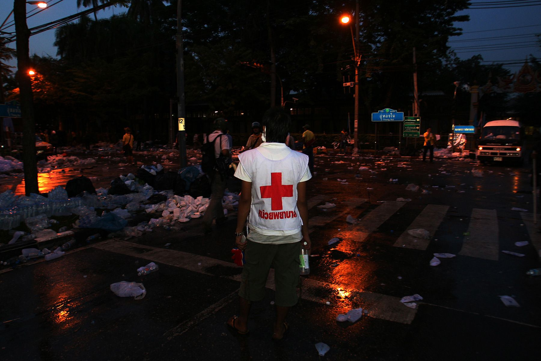 Red cross worker stands and looking for an injured person during crash between the People's Alliance for Democracy (PAD) and Police.