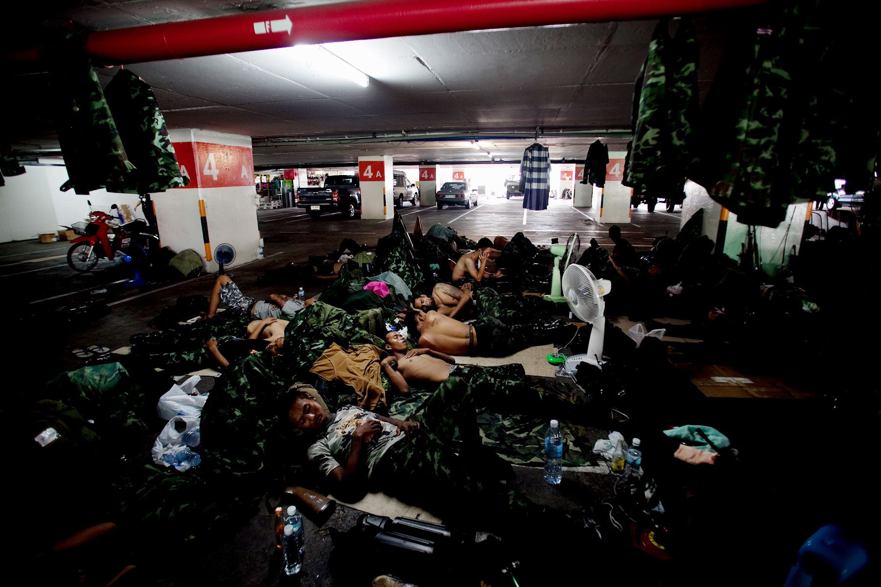 Soldiers catch up on sleep in the carpark of a central Bangkok department store near the United Front for Democracy AgainstDictatorship (UDD) demonstration site Sukhumbit Road.