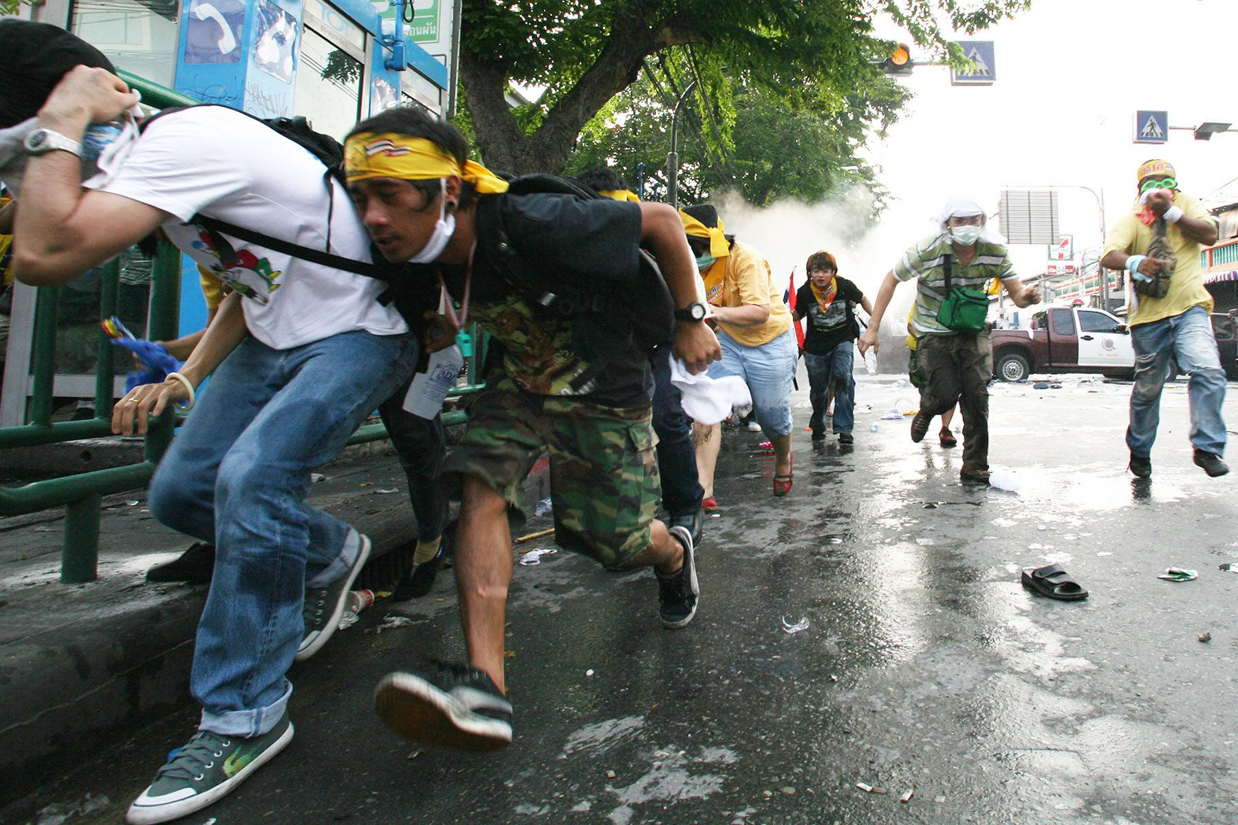 Demonstrators of People's Alliance for Democracy (PAD) shelter from tear gas.
