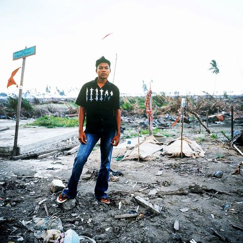 Amri stands in front of his family's gravesBanda Ache © 2004 Masaru Goto
