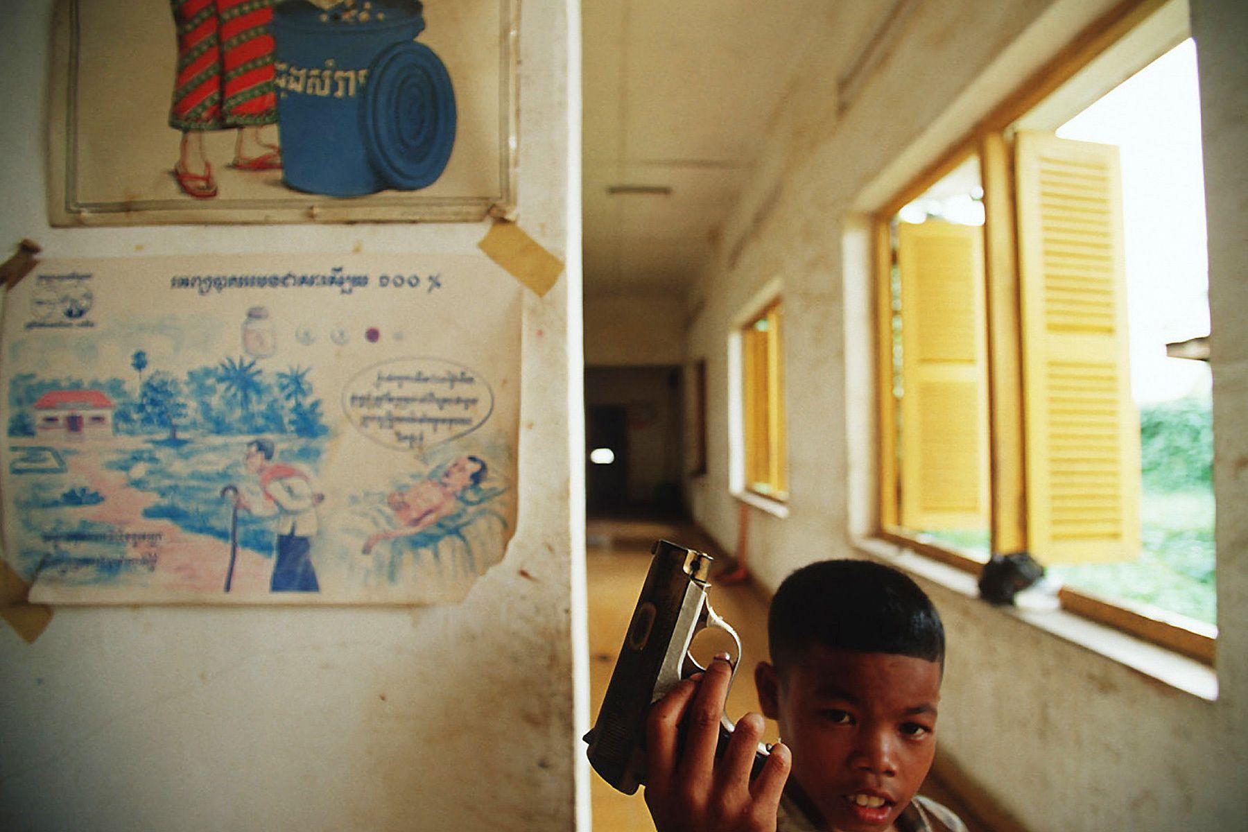 A boy with a toy gun, plays inside Aids ward.