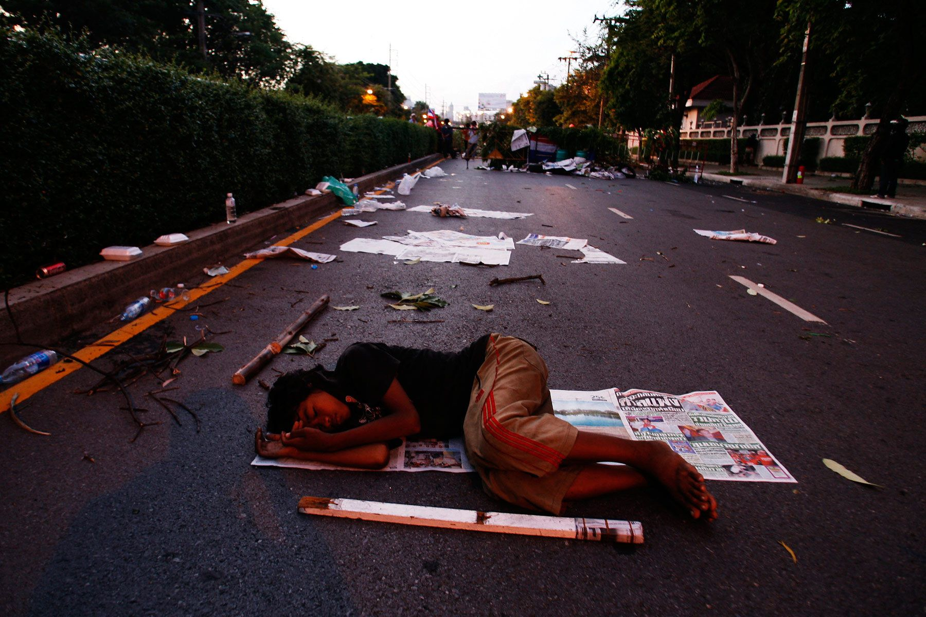 A ten-year-old boy protester from the Northeast sleeps on the street at dawn at a roadblock set by the anti-government United Front for Democracy against Dictatorship (UDD) in Bangkok. Two days of rioting by the UDD left two people dead and 100 injured.