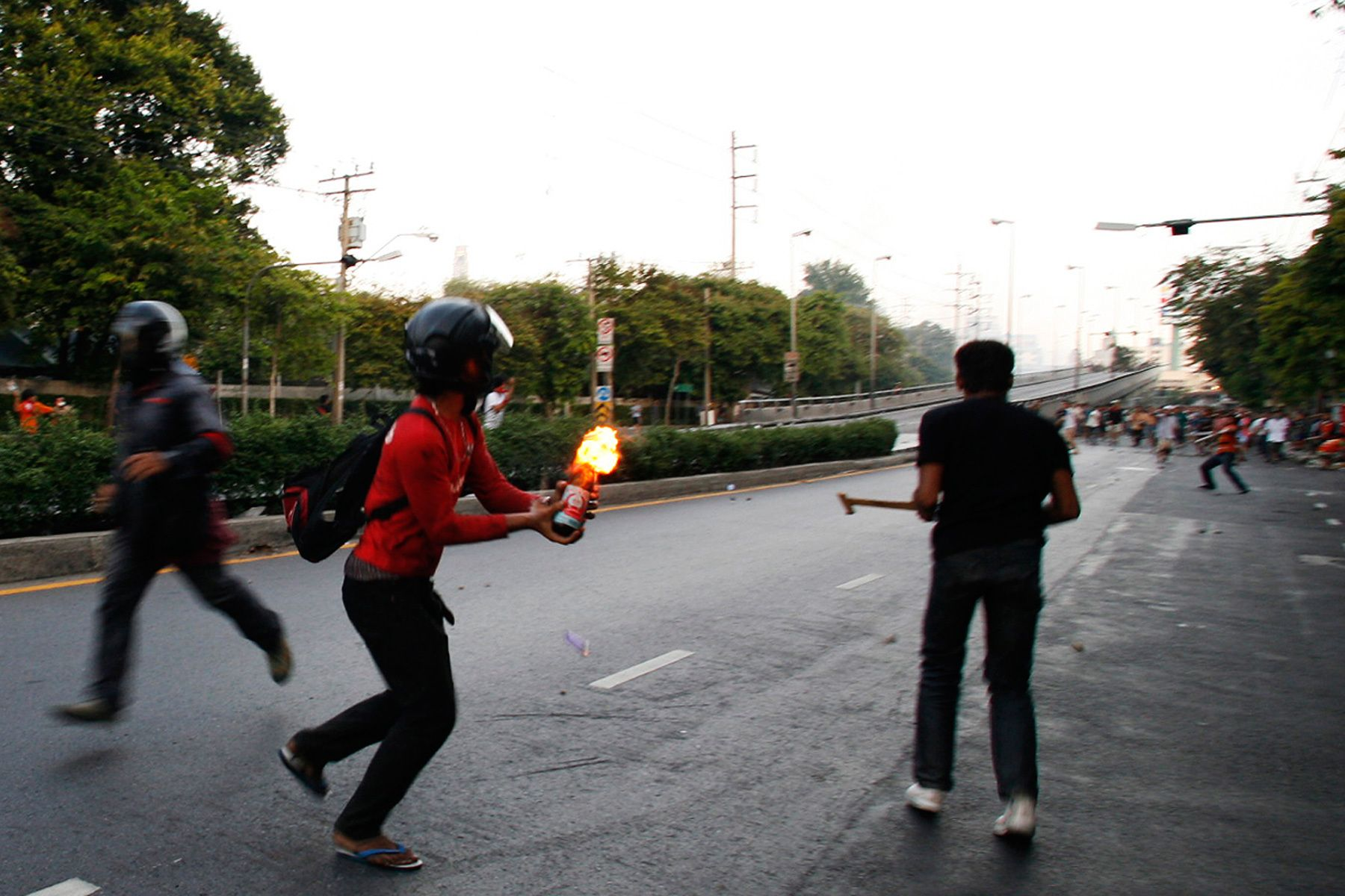 A member of the anti-government United Front for Democracy against Dictatorship (UDD) throw a petrol bomb during a street fight against residents.