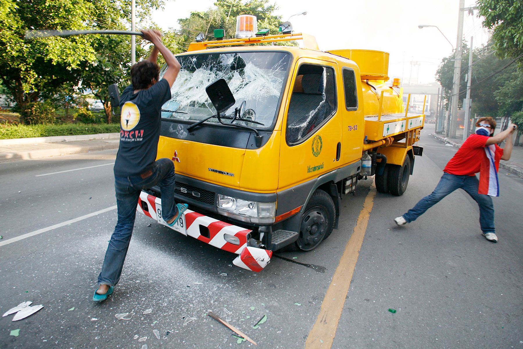 Members of the anti-government United Front for Democracy against Dictatorship (UDD) smash a firefighter truck sent after a bus was torched.