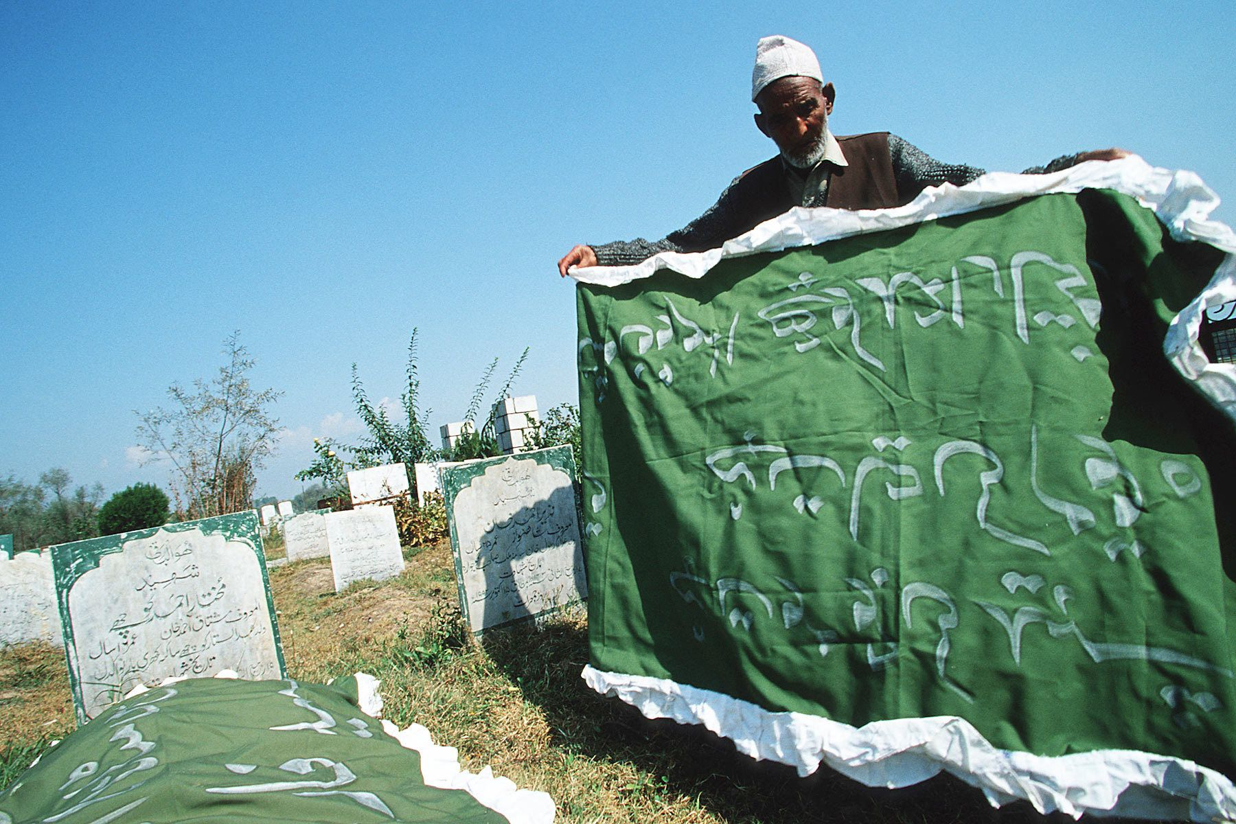 A man prays for his son at war victim cemetary
