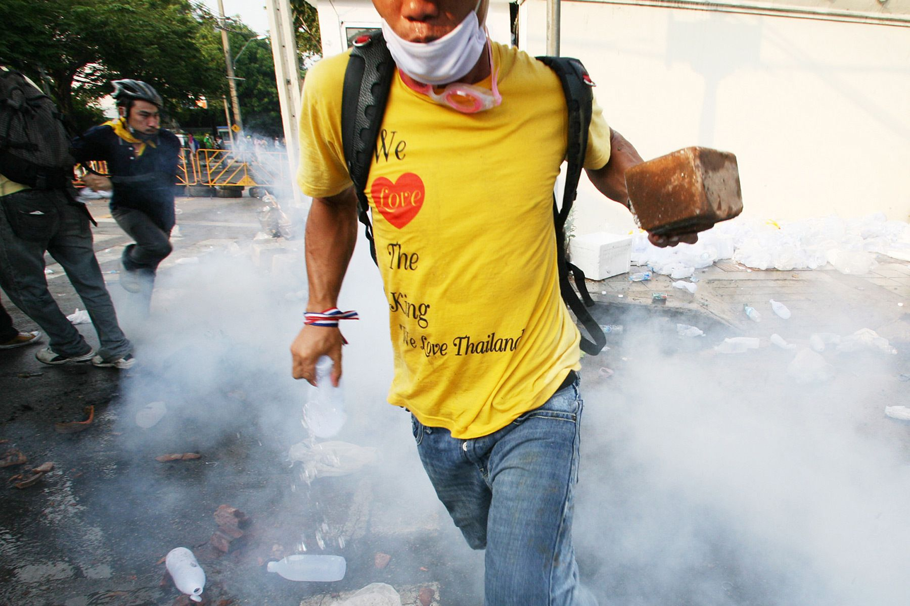 A demonstrator carrying a brick runs away in a cloud of tear gas during clashes between the People's Alliance for Democracy (PAD) and police.