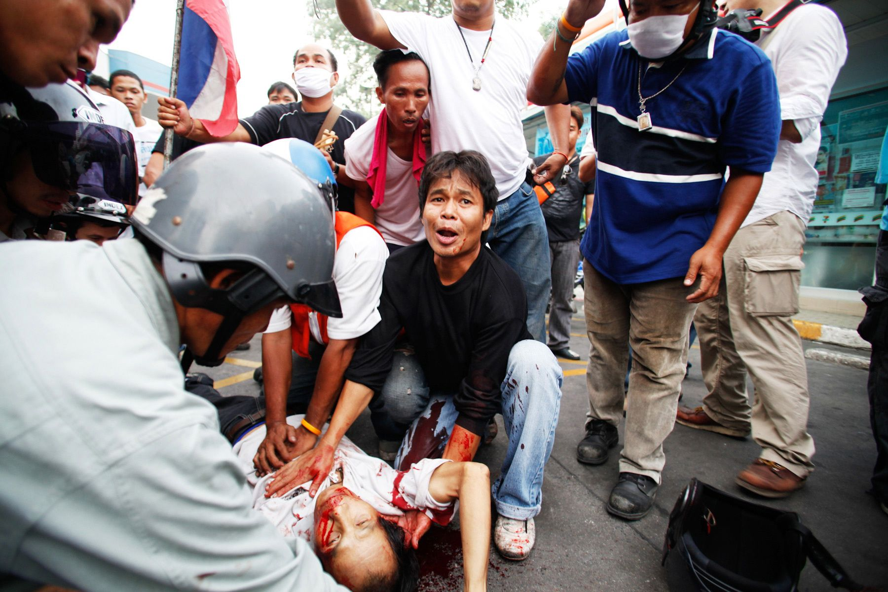 Members of The United Front for Democracy Against Dictatorship(UDD) aid a man shot by soldiers.