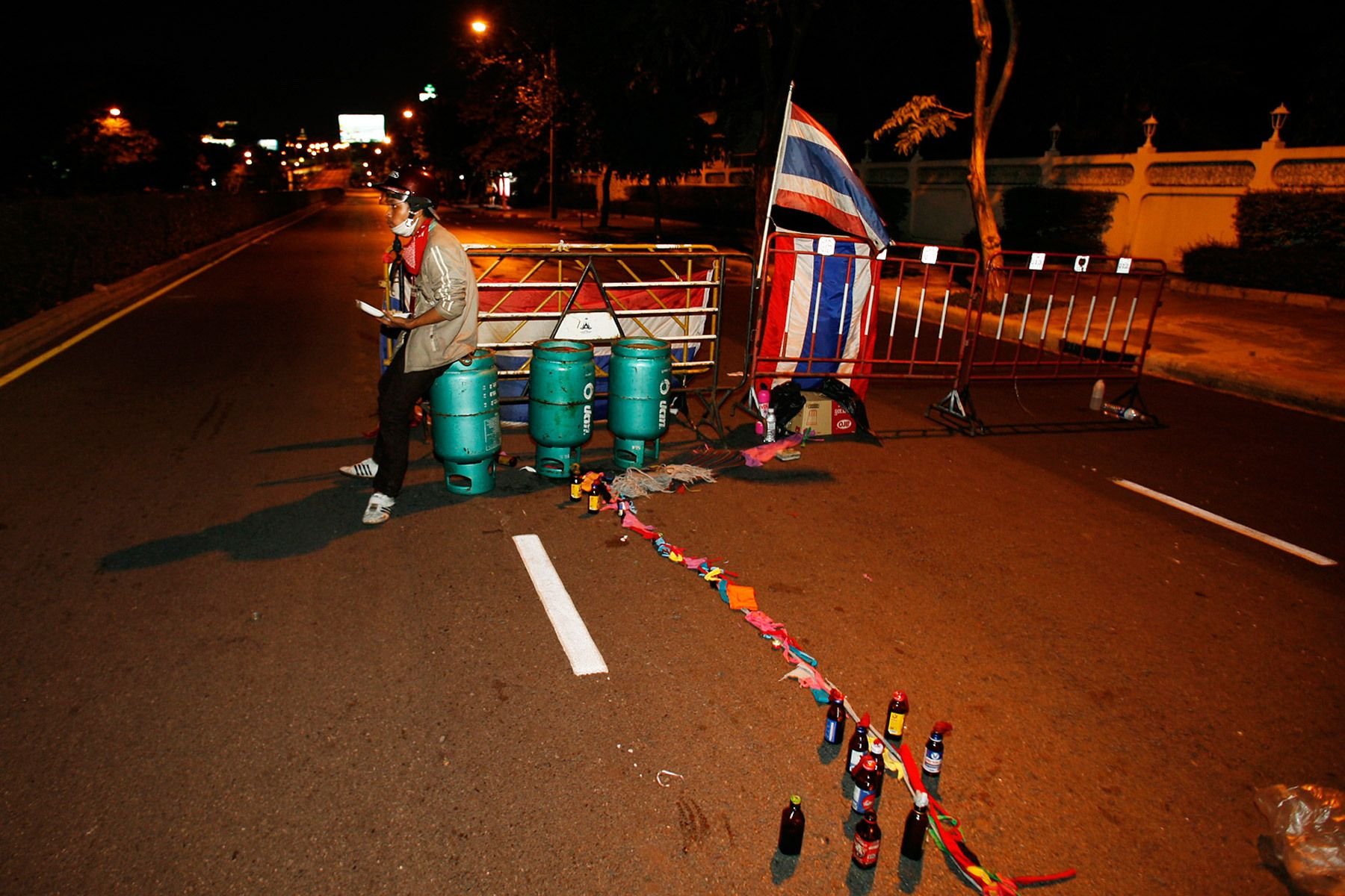 A member of the anti-government United Front for Democracy against Dictatorship (UDD) sits at a roadblock with a reserve of petrol bombs and gas bottles in Bangkok.