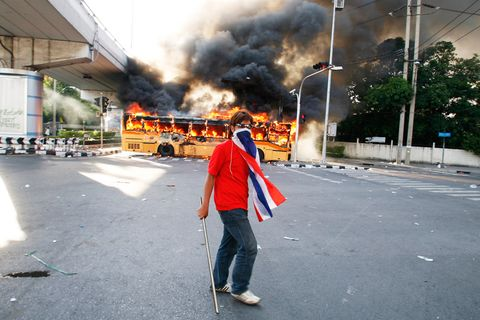 A member of the anti-government United Front for Democracy against Dictatorship (UDD) walks past a bus torched by the UDD in Bangkok. Two days of rioting by the UDD left two people dead and some 100 injured.April 2009