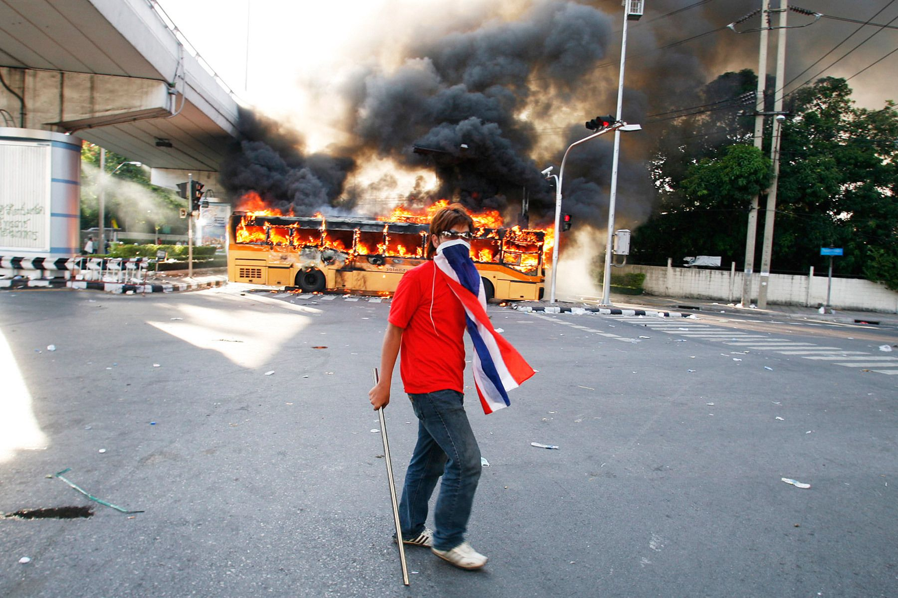 A member of the anti-government United Front for Democracy against Dictatorship (UDD) walks past a bus torched by the UDD in Bangkok. Two days of rioting by the UDD left two people dead and some 100 injured.