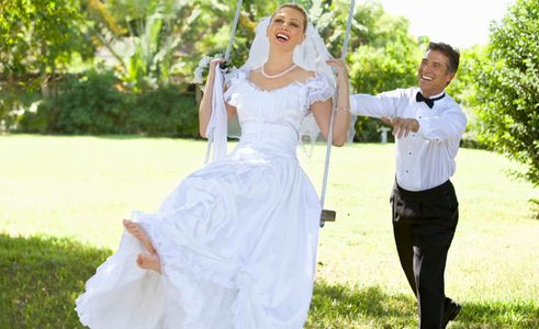 1Smiling_groom_pushes_his_bride_on_a_swing.jpg