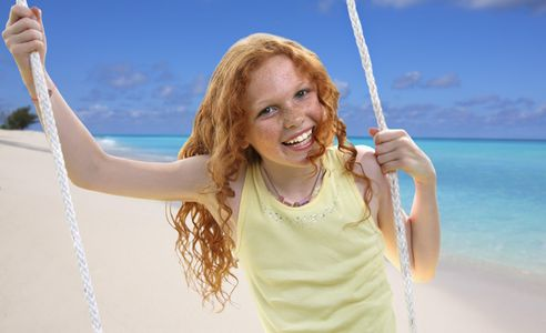 1Red_headed_girl_at_a_beach_on_a_swing.jpg