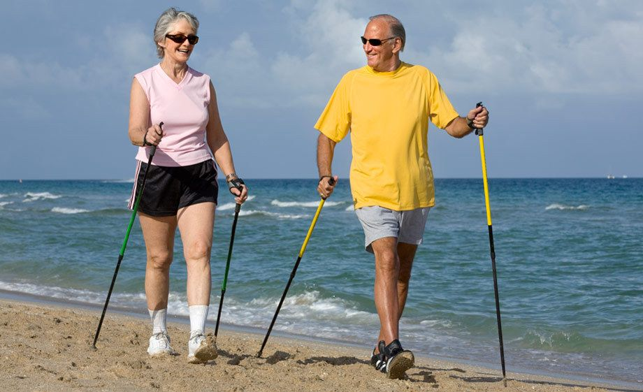 1Senior_couple_walking_with_ski_poles_on_the_beach.jpg