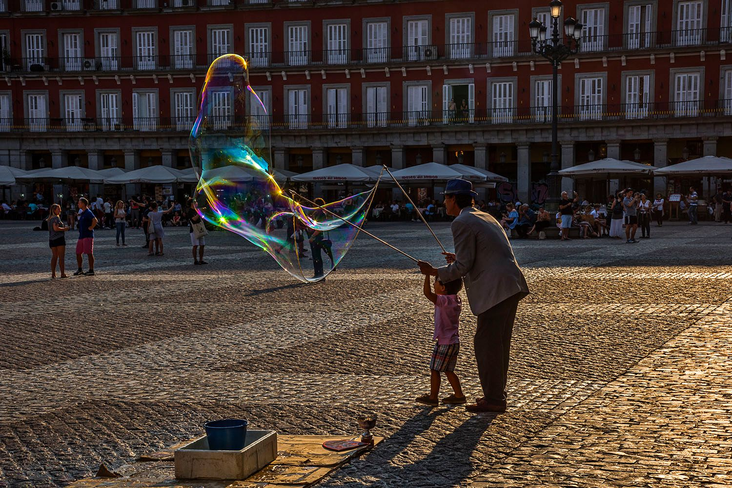 Man and child making large soap bubble