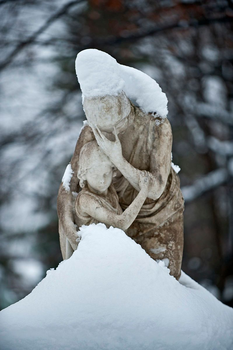 Statue of mother and child in snow