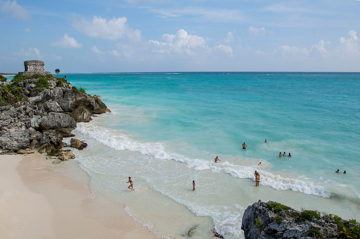 Tulum Mayan ruin with people swimming