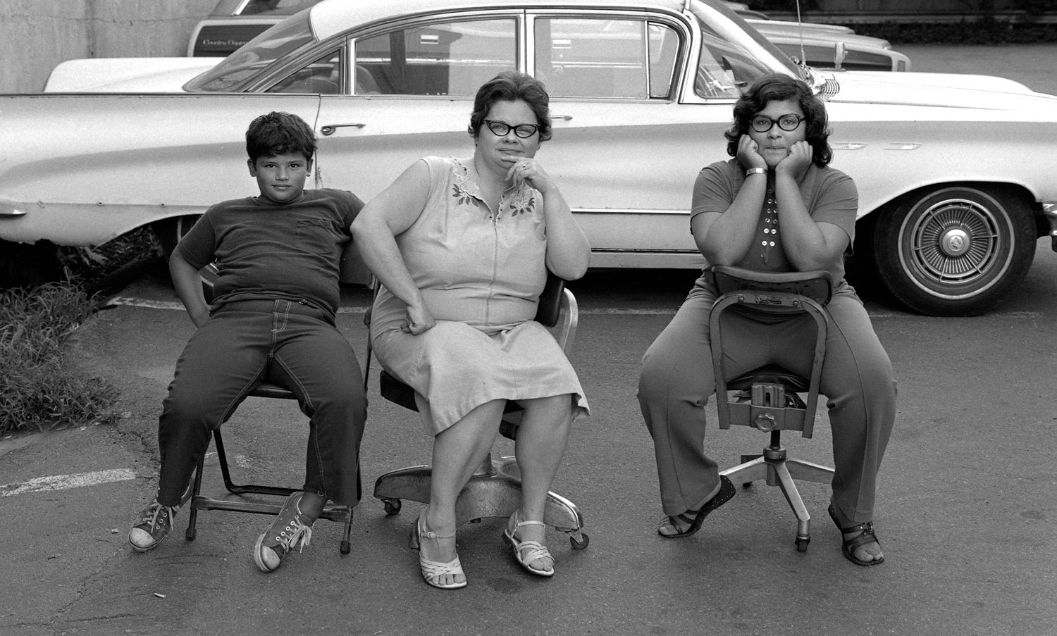 Family sitting on chairs in parking lot