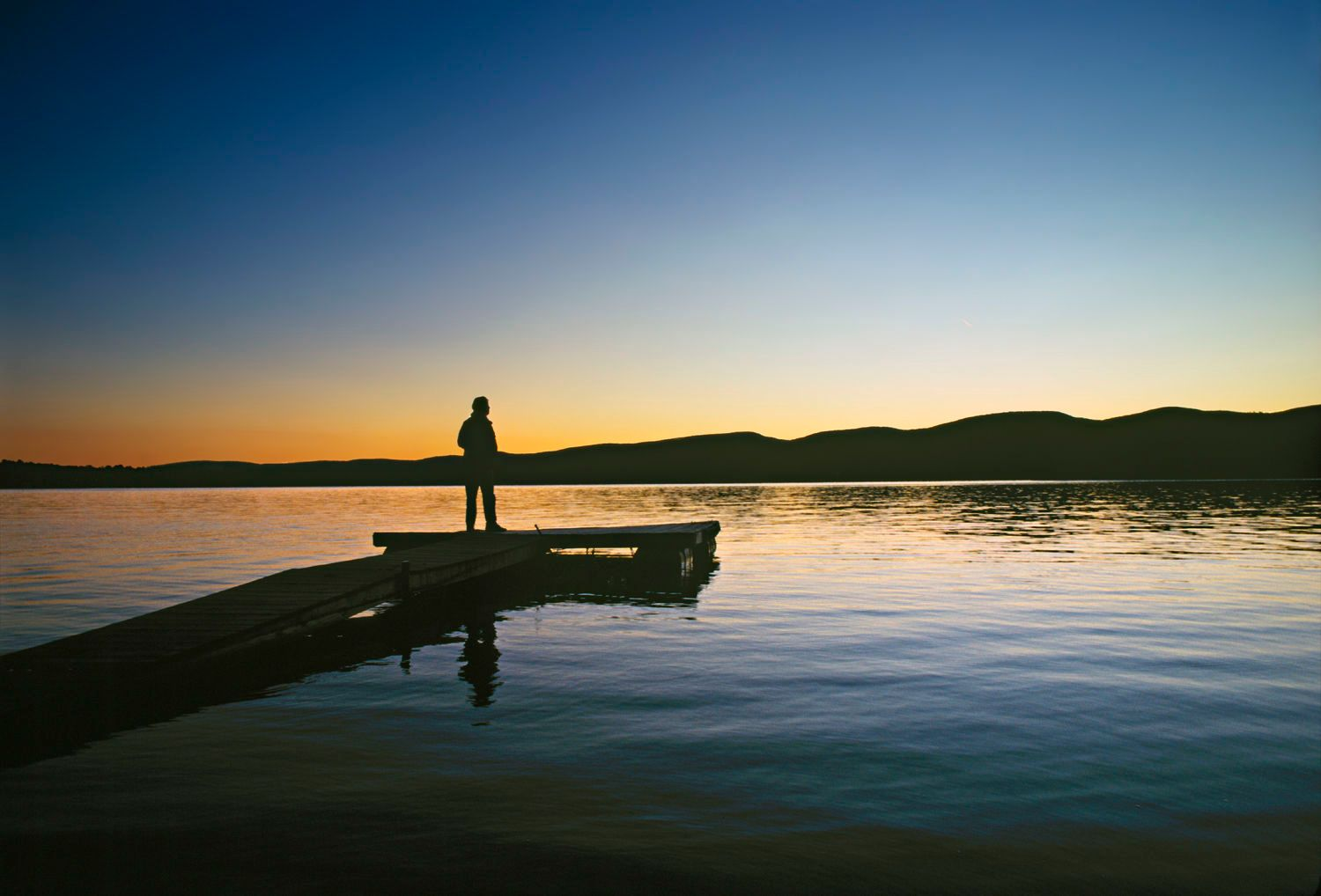 Person standing on dock at dusk