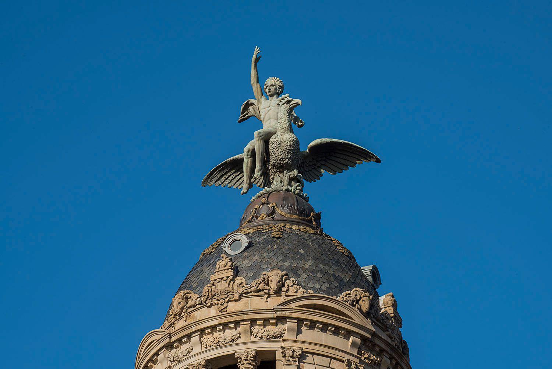 Bronze statue of a man  sitting on a bird