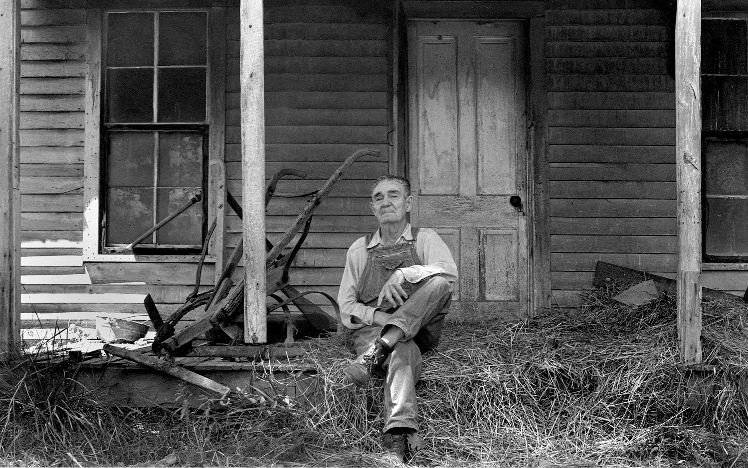 Farmer Sitting on Porch with hay and plow