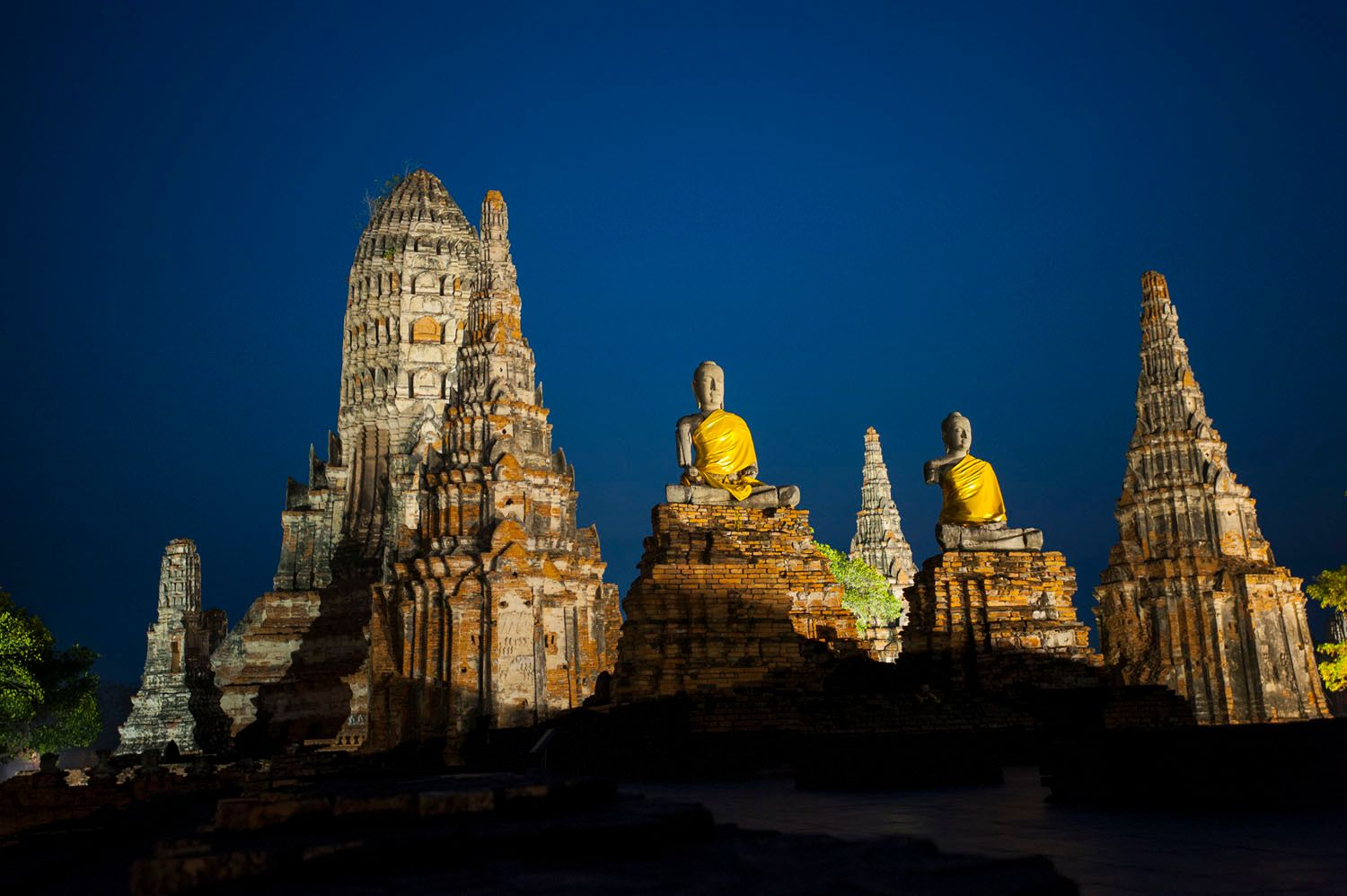 Buddha statues sitting amongst ancient ruins at dusk in Ayutthay