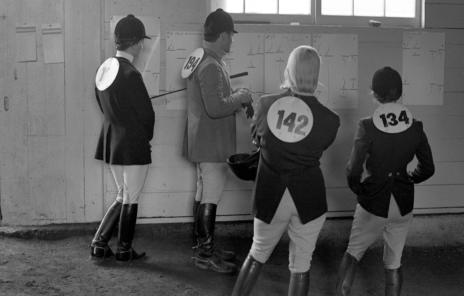 Equestrian Riders Looking at Chart