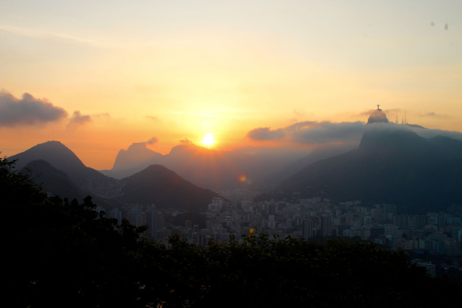 Cristo Redentor watches over the city as the sun sets.