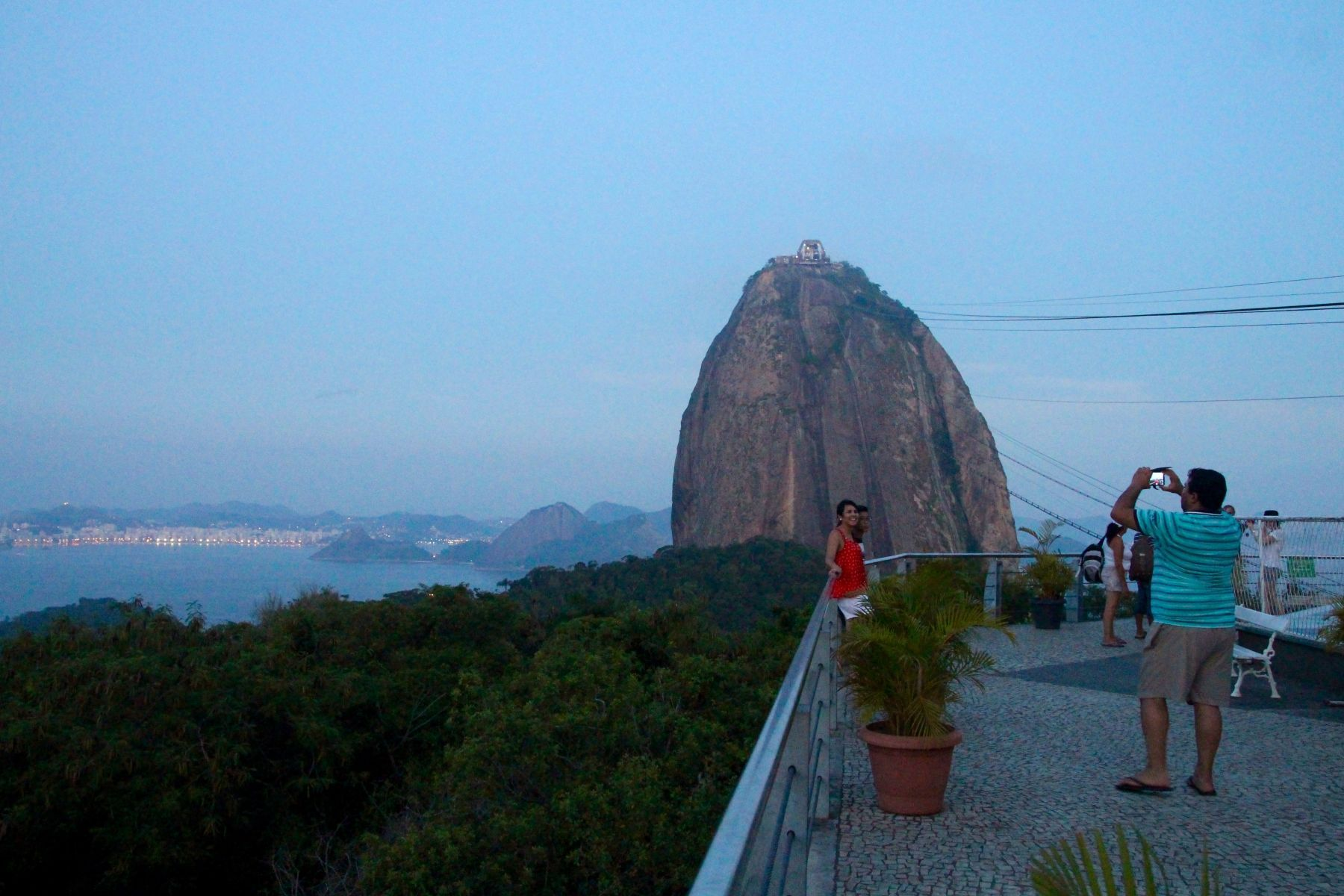 A young woman poses in front of Pão de Açúcar (Sugarloaf Mountain).