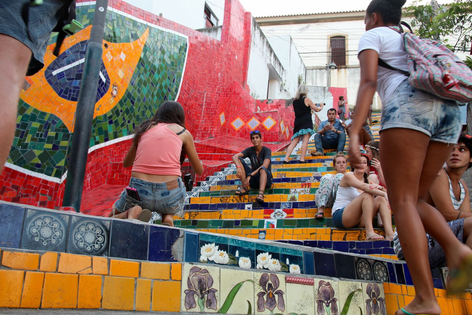 Travelers and locals alike snap photos on colorful steps of Escadaria Selarón.