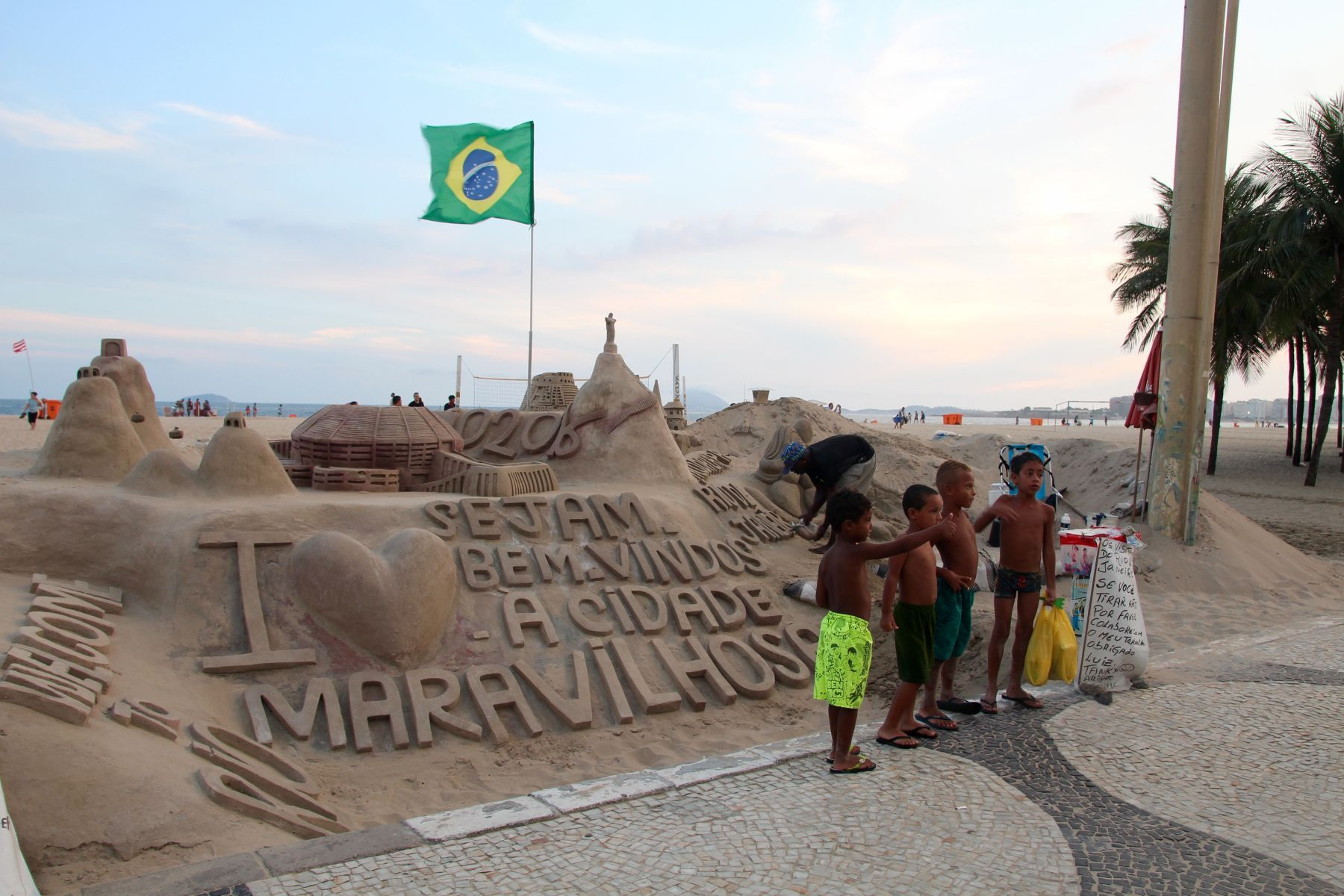 Young boys pose in front of an intricate sandcastle at Copacabana beach.