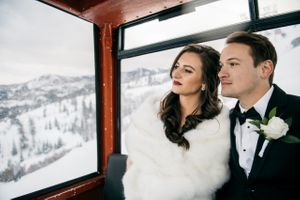 Bride and groom riding ski lift in snow