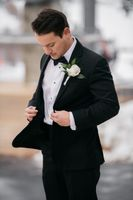 Groom in black suit with boutonniere