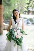 Bride with her bouquet by river outside