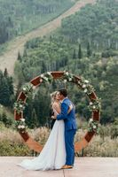 Mountain wedding ceremony with bride and groom kissing