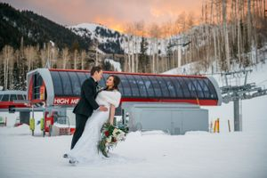 Bride and groom pose in front of ski lift