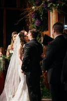 Bride and groom during ceremony kiss